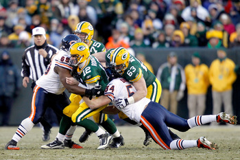 GREEN BAY, WI - JANUARY 02:  Quarterback Aaron Rodgers #12 of the Green Bay Packers is sacked by Henry Melton #69 and Brian Urlacher #54 of the Chicago Bears at Lambeau Field on January 2, 2011 in Green Bay, Wisconsin.  (Photo by Matthew Stockman/Getty Im