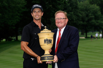 AKRON, OH - AUGUST 07:  (L-R) Adam Scott of Australia holds the Gary Player Cup trophy alongside Richard Hills, European Ryder Cup Director, after his four-stroke victory during the final round of the World Golf Championships-Bridgestone Invitational on t