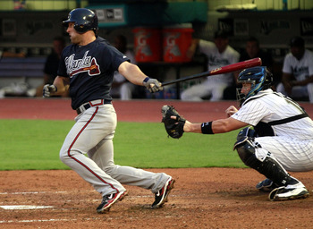 MIAMI GARDENS, FL - AUGUST 08:  Dan Uggla #26 of the Atlanta Braves gets a hit in the fifth inning against the Florida Marlins at Sun Life Stadium on August 8, 2011 in Miami Gardens, Florida.  (Photo by Marc Serota/Getty Images)