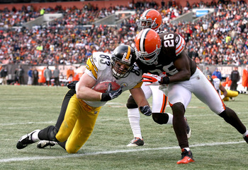 CLEVELAND, OH - JANUARY 02:  Tight end Heath Miller #83 of the Pittsburgh Steelers scores a touchdown as he is hit by defensive back Abram Elam #26 of the Cleveland Browns at Cleveland Browns Stadium on January 2, 2011 in Cleveland, Ohio.  (Photo by Matt