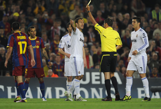 BARCELONA, SPAIN - MAY 03:  Referee Frank De Bleeckere shows the yellow card to Carvalho of Real Madrid (C) during the UEFA Champions League Semi Final second leg match between Barcelona and Real Madrid at the Nou Camp on May 3, 2011 in Barcelona, Spain.