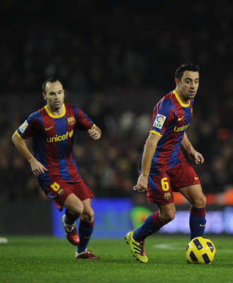 BARCELONA, SPAIN - JANUARY 12:  Xavi Hernandez of FC Barcelona (R) and his teammate Andres Iniesta in action during the Copa del Rey quarter final first leg match between FC Barcelona and Betis at Camp Nou on January 12, 2011 in Barcelona, Spain. Barcelon