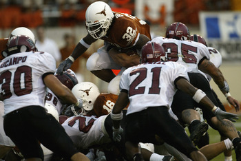 AUSTIN, TX - AUGUST 31:  Running back Cedric Benson #32 of the University of Texas at Austin Longhorns leaps over the New Mexico State University Aggies during the game Texas Memorial Stadium on August 31, 2003 in Austin, Texas. Texas defeated New Mexico