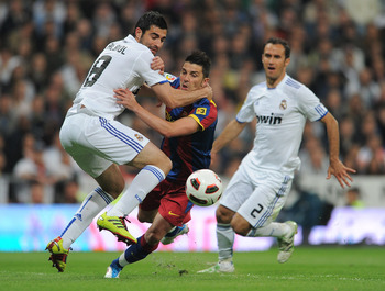 MADRID, SPAIN - APRIL 16:  Raul Albiol (L) of Real Madrid fouls David Villa (C) of Barcelona in the penalty aeria as Ricardo Carvalho looks on during the la Liga match between Real Madrid and Barcelona at Estadio Santiago Bernabeu on April 16, 2011 in Mad