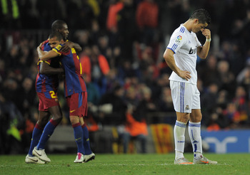 BARCELONA, SPAIN - NOVEMBER 29:  Cristiano Ronaldo of Real Madrid (R) looks down as Eric Abidal and Dani Alves of Barcelona celebrates the fifth goal  against Real Madrid during the La Liga match between Barcelona and Real Madrid at the Camp Nou Stadium o