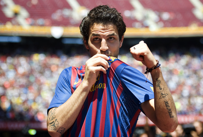 BARCELONA, SPAIN - AUGUST 15:  Cesc Fabregas kis the t-shirt during his presentation as the new signing for FC Barcelona at Camp Nou sports complex on August 15, 2011 in Barcelona, Spain.  (Photo by David Ramos/Getty Images)