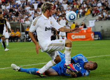 LOS ANGELES, CA - JULY 16:  Fabio Coentrao #15 of Real Madrid crashes with goalkeeper Josh Saunders #12 against Los Angeles Galaxy during the Herbalife World Challenge 2011 friendly soccer game at Los Angeles Memorial Coliseum on July 16, 2011 in Los Ange