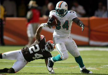 MIAMI - DECEMBER 05:  Running back Ricky Williams #34 of the Miami Dolphins is brought down by Sheldon Brown #24 of the Cleveland Browns at Sun Life Stadium on December 5, 2010 in Miami, Florida.  (Photo by Marc Serota/Getty Images)