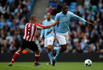 MANCHESTER, ENGLAND - APRIL 03:  Yaya Toure of Manchester City is challenged by Lee Cattermole of Sunderland during the Barclays Premier League match between Manchester City and Sunderland at the City of Manchester Stadium on April 3, 2011 in Manchester,