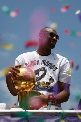 LOS ANGELES, CA - JUNE 21:  Confetti thrown from the crowd falls around Los Angeles Lakers guard Kobe Bryant as he holds the championship trophy while riding in the victory parade for the NBA basketball champion team on June 21, 2010 in Los Angeles, Calif