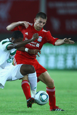 GUANGZHOU, CHINA - JULY 13:  John Flanagan (R) of Liverpool challenges Diakite (L) of Guangdong Sunray Cave during the pre-season friendly match between Guangdong Sunray Cave and Liverpool at Guangdong Provincial People's Stadium on July 13, 2011 in Guang