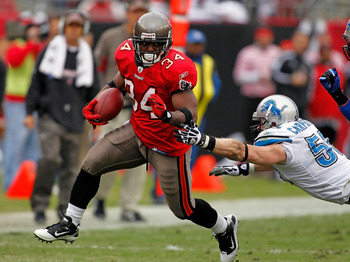 TAMPA, FL - DECEMBER 19:  Running back Earnest Graham #34 of the Tampa Bay Buccaneers runs through the tackle of linebacker Bobby Carpenter #59 of the Detroit Lions during the game at Raymond James Stadium on December 19, 2010 in Tampa, Florida.  (Photo b