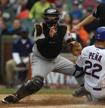 CHICAGO, IL - MAY 29: Carlos Pena #22 of the Chicago Cubs slides safely into home to score a run ahead of the tag by Ryan Doumit #41 of the Pittsburgh Pirates at Wrigley Field on May 29, 2011 in Chicago, Illinois. Doumit was injured on the play and left t