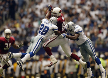 IRVING, TX - OCTOBER 5:  Darren Woodson #28 and Roy Williams #31 of the Dallas Cowboys tackle tight end Freddie Jones #85 of the Arizona Cardinals on the incomplete pass at Texas Stadium on October 5, 2003 in Irving, Texas.  The Cowboys defeated the Cardi