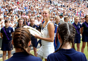 LONDON, ENGLAND - JULY 02:  Petra Kvitova of the Czech Republic holds her Championship trophy as she walks off court after winning her Ladies' final round match against Maria Sharapova of Russia on Day Twelve of the Wimbledon Lawn Tennis Championships at