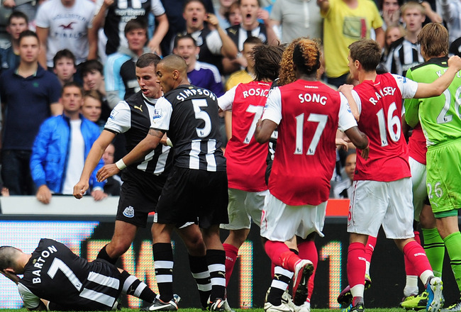 NEWCASTLE UPON TYNE, ENGLAND - AUGUST 13: Joey Barton of Newcastle goes to ground clutching his head after a clash with Gervinho of Arsenal during the Barclays Premier League match between Newcastle United and Arsenal at St James' Park on August 13, 2011