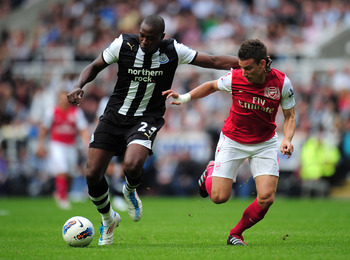 NEWCASTLE UPON TYNE, ENGLAND - AUGUST 13:  Shola Ameobi of Newcastle United is challenged by Laurent Koscielny of Arsenal during the Barclays Premier League match between Newcastle United and Arsenal at St James' Park on August 13, 2011 in Newcastle upon