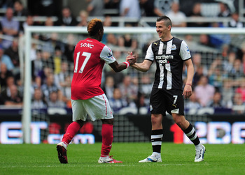 NEWCASTLE UPON TYNE, ENGLAND - AUGUST 13:  Joey Barton of Newcastle shakes hands with Alex Song of Arsenal during the Barclays Premier League match between Newcastle United and Arsenal at St James' Park on August 13, 2011 in Newcastle upon Tyne, England.