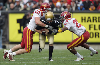 BOULDER, CO - NOVEMBER 13:  Quarterback Cody Hawkins #7 of the Colorado Buffaloes scrambles and is tackled by Jake Knott #20 and Leonard Johnson #23 of the Iowa State Cyclones at Folsom Field on November 13, 2010 in Boulder, Colorado. Colorado defeated Io