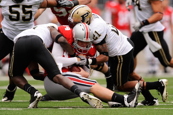 COLUMBUS, OH - OCTOBER 23:  Quarterback Joe Bauserman #14 of the Ohio State Buckeyes is sacked by Charlton Williams #15 and Ricardo Allen #21 of the Purdue Boilermakers in the second half at Ohio Stadium on October 23, 2010 in Columbus, Ohio.  (Photo by J