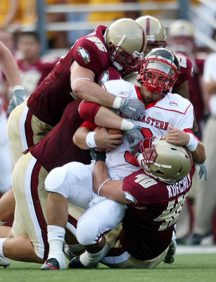 CHESTNUT HILL, MA - SEPTEMBER 05:  Matt Carroll #3 of the Northeastern Huskies is tackled by Dillon Quinn #92,Kaleb Ramsey #96 and Luke Kuechly #40  of the Boston College Eagles on September 5, 2009 at Alumni Stadium in Chestnut Hill, Massachusetts.  (Pho