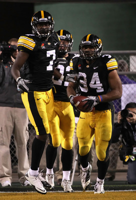 TEMPE, AZ - DECEMBER 28:  Runningback Marcus Coker #34 of the Iowa Hawkeyes celebrates with teammates with Marvin McNutt #1 and Colin Sandeman #22 after scoring on a 64 yard rushing touchdown against the Missouri Tigers during the second quarter of the In