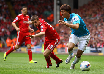 LIVERPOOL, ENGLAND - AUGUST 13:  Ji Dong-Won of Sunderland goes past John Flanagan of Liverpool during the Barclays Premier League match between Liverpool and Sunderland at Anfield on August 13, 2011 in Liverpool, England.  (Photo by Clive Brunskill/Getty