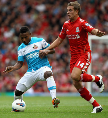 LIVERPOOL, ENGLAND - AUGUST 13:  Jordan Henderson of Liverpool is tackled by Stephane Sessegnon of Sunderland during the Barclays Premier League match between Liverpool and Sunderland at Anfield on August 13, 2011 in Liverpool, England.  (Photo by Clive B