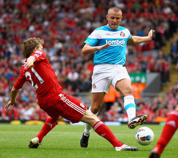 LIVERPOOL, ENGLAND - AUGUST 13:  Leiva Lucas of Liverpool tackles Lee Cattermole of Sunderland during the Barclays Premier League match between Liverpool and Sunderland at Anfield on August 13, 2011 in Liverpool, England.  (Photo by Clive Brunskill/Getty