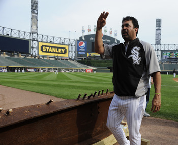 CHICAGO, IL - AUGUST 01: Ozzie Guillen #13 manager of the Chicago White Sox looks at an 8-foot steel I-beam from the World Trade Center wreckage on display during the Chicago White Sox and New York Yankees game on August 1, 2011 at U.S. Cellular Field in