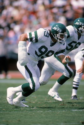 1985:  Defensive end Mark Gastineau #99 of the New York Jets wears a cast on his right arm as he runs on the field during a game in 1985.  (Photo by Rick Stewart/Getty Images)