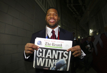 GLENDALE, AZ - FEBRUARY 03:  Defensive end Michael Strahan #92 of the New York Giants holds a newspaper with the headline 'GIANTS WIN!' after the Giants defeated the New England Patriots 17-14 during Super Bowl XLII on February 3, 2008 at the University o