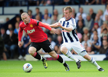 WEST BROMWICH, ENGLAND - AUGUST 14:  Chris Brunt of West Bromwich Albion challenges Wayne Rooney of Manchester United during the Barclays Premier League match between West Bromwich Albion and Manchester United at The Hawthorns on August 14, 2011 in West B