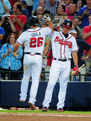ATLANTA - AUGUST 13: Dan Uggla #26 of the Atlanta Braves is congratulated by Chipper Jones #10 after hitting a home run against the Chicago Cubs at Turner Field on August 13, 2011 in Atlanta, Georgia. (Photo by Scott Cunningham/Getty Images)
