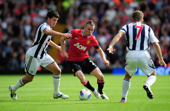 WEST BROMWICH, ENGLAND - AUGUST 14: Tom Cleverley of Manchester United takes the ball past  Shane Long (L) of West Bromwich Albion during the Barclays Premier League match between West Bromwich Albion and Manchester United at The Hawthorns on August 14, 2