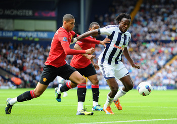 WEST BROMWICH, ENGLAND - AUGUST 14: Somen Tchoyi of West Bromwich Albion is closed down by Chris Smalling of Manchester United during the Barclays Premier League match between West Bromwich Albion and Manchester United at The Hawthorns on August 14, 2011