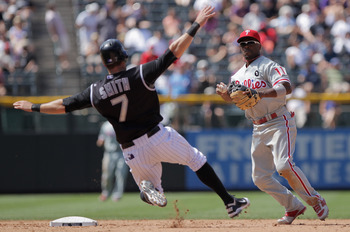 DENVER, CO - AUGUST 03:  Shortstop Jimmy Rollins #11 of the Philadelphia Phillies turns a double play on Seth Smith #7 of the Colorado Rockies on a ball hit by Ian Stewart of the Rockies at Coors Field on August 3, 2011 in Denver, Colorado.  (Photo by Dou