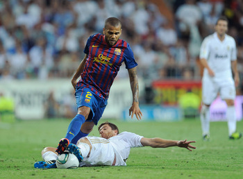 MADRID, SPAIN - AUGUST 14: Xabi Alonso (R) of Real Madrid tackles Dani Alves of Barcelona during the Super Cup first leg match between Real Madrid and Barcelona at Estadio Santiago Bernabeu on August 14, 2011 in Madrid, Spain.  (Photo by Denis Doyle/Getty
