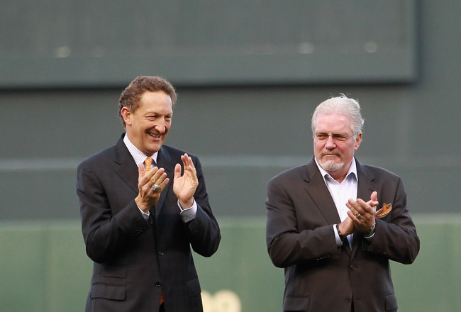 SAN FRANCISCO, CA - JUNE 09:  (from left) San Francisco Giants CEO Bill Newcomb, team president Larry Baer, general manager Brian Sabean, and manager Bruce Bochy applaud as Edgar Renteria #16 of the Cincinnati Reds runs on to the field to receive his Worl