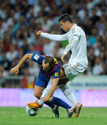MADRID, SPAIN - AUGUST 14:  Cristiano Ronaldo (R) of Real Madrid tackles Andres Iniesta of Barcelona during the Super Cup first leg match between Real Madrid and Barcelona at Estadio Santiago Bernabeu on August 14, 2011 in Madrid, Spain.  (Photo by Denis