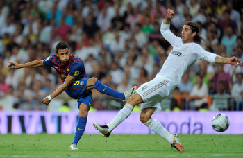 MADRID, SPAIN - AUGUST 14:  Alexis Sanchez (L) of Barcelona fires a shot past Sergio Ramos of Real Madrid during the Super Cup first leg match between Real Madrid and Barcelona at Estadio Santiago Bernabeu on August 14, 2011 in Madrid, Spain.  (Photo by D