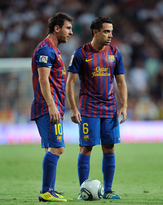 MADRID, SPAIN - AUGUST 14: Xavi Hernandez (R) and Leo Messi of Barcelona line up a free kick during the Super Cup first leg match between Real Madrid and Barcelona at Estadio Santiago Bernabeu on August 14, 2011 in Madrid, Spain.  (Photo by Denis Doyle/Ge