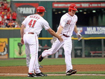 CINCINNATI, OH - AUGUST 13:  Jay Bruce #32 of the Cincinnati Reds is congratulated by third base coach Mark Berry #41 after hitting a home run during the game against the San Diego Padres at Great American Ball Park on August 13, 2011 in Cincinnati, Ohio.