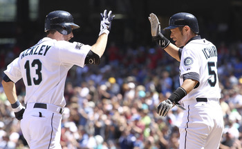 SEATTLE - JULY 30:  Dustin Ackley #13 of the Seattle Mariners is congratulated by Ichiro Suzuki #51 after hitting a two-run homer against the Tampa Bay Rays at Safeco Field on July 30, 2011 in Seattle, Washington. The Mariners defeated the Rays 3-2. (Phot