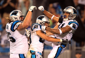 CHARLOTTE, NC - AUGUST 13:  Kealoha Pilares #81 of the Carolina Panthers celebrates with teammates after scoring a touchdown during their preseason game against the New York Giants at Bank of America Stadium on August 13, 2011 in Charlotte, North Carolina
