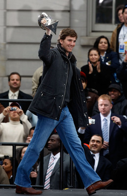 NEW YORK - FEBRUARY 05:  Quarterback Eli Manning holds the Vince Lombardi trophy up as he takes the stage during the New York Giants Super Bowl XLII victory parade reception at City Hall February 5, 2008 in New York City.  (Photo by Nick Laham/Getty Image