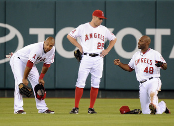 ANAHEIM, CA - AUGUST 15:  (L-R) Vernon Wells #10 of the Los Angeles Angels of the Anaheim, Peter Bourjos #25 and Torii Hunter #48 wait during a pitching change against the Texas Rangers during the fifth inning at Angel Stadium of Anaheim on August 15, 201