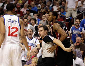 PHILADELPHIA, PA - APRIL 24: Official David Guthrie (C) seperates Evan Turner #12 of the Philadelphia 76ers and James Jones #22 of the Miami Heat (R) after an altercation during the first half of Game Four of the Eastern Conference Quarterfinals at Wells