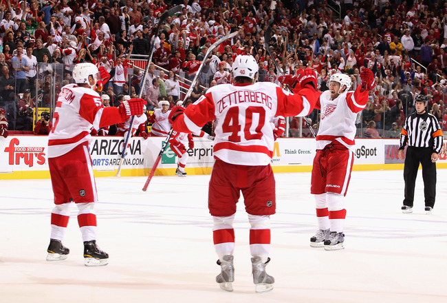GLENDALE, AZ - OCTOBER 16:  Niklas Kronwall #55 (R) of the Detroit Red Wings celebrates with teammates Nicklas Lidstrom #5 and Henrik Zetterberg #40 after Kronwall scored the game winning power play goal in overtime against the Phoenix Coyotes during the