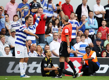 LONDON, ENGLAND - AUGUST 13:  Clint Hill (L) of Queens Park Rangers is shown the red card by referee Martin Atkinson after a challenge on Martin Petrov of Bolton during the Barclays Premier League match between Queens Park Rangers and Bolton Wanderers at